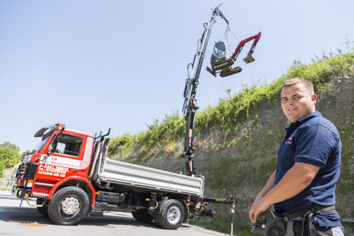 Mitarbeiter mit LKW Scania im Hintergrund