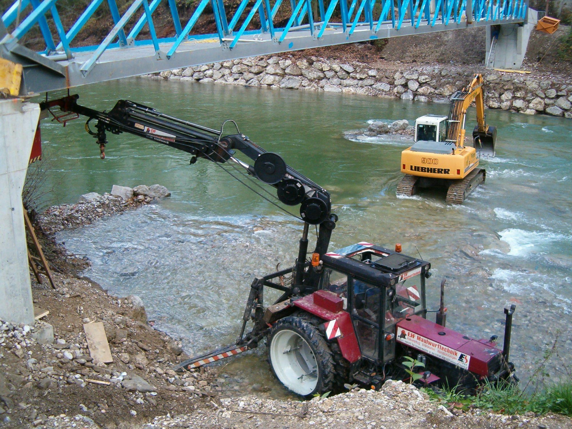 Traktor mit Kran bei Brückenarbeiten